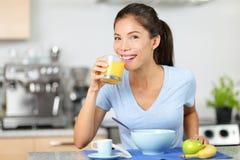 Succo d'arancia bevente della donna che mangia prima colazione Fotografia Stock