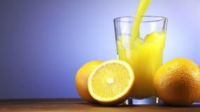 Succo d'arancia che versa in vetro sul fondo di colore stock footage