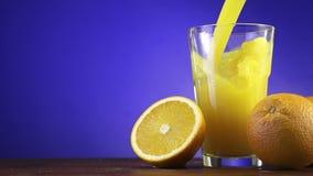 Succo d'arancia che versa in vetro sul fondo di colore video d archivio