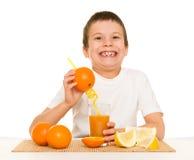 Succo d'arancia della bevanda del ragazzo con una paglia Fotografia Stock
