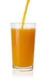 Succo d'arancia di versamento in vetro su fondo bianco Immagini Stock