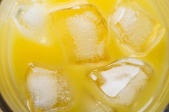 Succo d'arancia e cubetti di ghiaccio sopraelevati Fotografie Stock