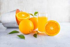 Succo d'arancia ed arancia freschi in un canestro su un BAC di legno bianco immagine stock