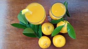 succo d'arancia freddo nei frutti arancio di vetro e freschi su pronto di legno ad essere goduto di immagine stock