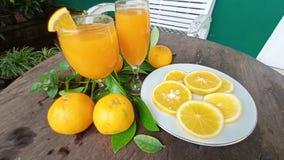 succo d'arancia freddo nei pezzi arancio di vetro e freschi su un piatto pronto ad essere goduto di immagini stock