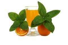 Succo d'arancia fresco con la menta in una tazza di vetro isolata su fondo bianco Arance e succo freschi su un fondo bianco, vist Immagine Stock Libera da Diritti