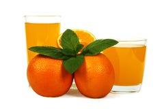 Succo d'arancia fresco con la menta in una tazza di vetro isolata su fondo bianco Arance e succo freschi su un fondo bianco, vist Immagini Stock