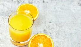 Succo d'arancia fresco del succo in un vetro con le fette arancio su cemento leggero Vista orizzontale detox Primo piano Copi lo  immagine stock libera da diritti
