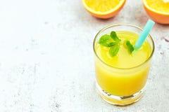 Succo d'arancia fresco del succo in un vetro con le fette arancio su cemento leggero Vista orizzontale detox Primo piano Copi lo  fotografie stock