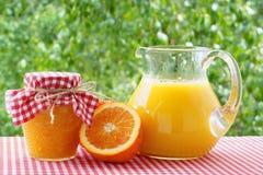 Succo d'arancia, inceppamento, metà arancio su una tovaglia a quadretti rossa Immagini Stock Libere da Diritti