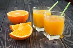 Succo d'arancia nei vetri su una tavola di legno Fotografie Stock Libere da Diritti