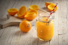 Succo d'arancia su una tavola di legno nella priorità alta Fotografia Stock Libera da Diritti