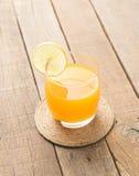Succo d'arancia sul fondo di legno della tavola Fotografia Stock