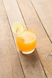 Succo d'arancia sul fondo di legno della tavola Fotografie Stock