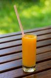 Succo d'arancia sul fondo di legno della tavola Succo su un fondo verde all'aperto Fotografia Stock