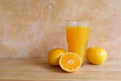 Succo d'arancia in una frutta fresca di vetro e sulla tavola Fotografia Stock