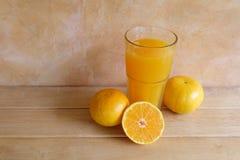 Succo d'arancia in una frutta fresca di vetro e sulla tavola Fotografie Stock