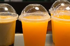 Succo d'arancia in vetro di plastica immagini stock