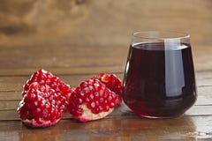 Succo delizioso dal melograno maturo in bello vetro su legno Fotografie Stock