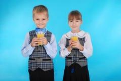 Succo della bevanda del ragazzo e della ragazza Immagini Stock Libere da Diritti
