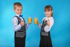Succo della bevanda del ragazzo e della ragazza Immagine Stock