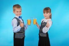 Succo della bevanda del ragazzo e della ragazza Fotografia Stock Libera da Diritti