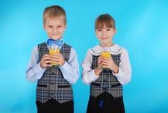 Succo della bevanda del ragazzo e della ragazza Fotografie Stock