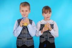 Succo della bevanda del ragazzo e della ragazza Fotografia Stock