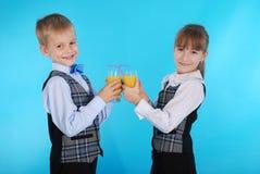 Succo della bevanda del ragazzo e della ragazza Immagini Stock