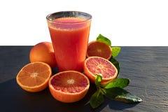 Succo delle arance sanguigne rosso sangui su un piatto dell'ardesia fotografia stock libera da diritti