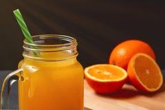 Succo di agrumi appena fatto dalle arance, dal pompelmo e dalla calce in una barattolo-tazza con una fine della paglia su fotografia stock