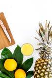 Succo di ananas fresco in ananas vicino di vetro e foglie di palma sul copyspace bianco di vista superiore del fondo Fotografie Stock