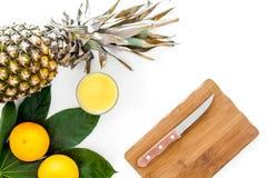 Succo di ananas fresco in ananas vicino di vetro e foglie di palma sulla vista superiore del fondo bianco Immagine Stock