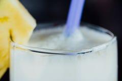 Succo di ananas in un vetro, nel pezzo di frutta ed in un tubo Fotografie Stock