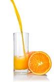 Succo di arancia che poring nel vetro immagini stock