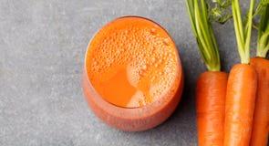 Succo di carota in alimento sano delle carote di vetro e fresche su una vista superiore del fondo di pietra grigio Immagini Stock Libere da Diritti
