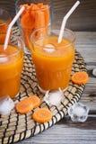 Succo di carota con ghiaccio in un vetro trasparente Fotografie Stock