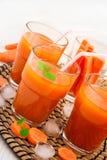 Succo di carota con polpa, ghiaccio e la menta su un fondo bianco Fotografie Stock Libere da Diritti