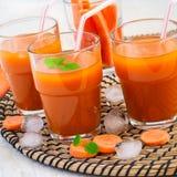 Succo di carota con polpa, ghiaccio e la menta su un fondo bianco Immagine Stock Libera da Diritti