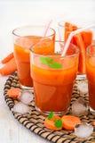 Succo di carota con polpa, ghiaccio e la menta su un fondo bianco Fotografia Stock
