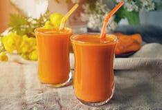 Succo di carota in due tazze di vetro su un fondo delle carote e dei fiori nel primo mattino La struttura orizzontale Fotografia Stock