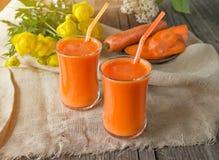 Succo di carota in due tazze di vetro su un fondo delle carote e dei fiori nel primo mattino La struttura orizzontale Immagini Stock