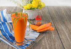 Succo di carota in due vetri su un fondo delle carote e dei fiori nel primo mattino Una struttura orizzontale Fotografia Stock