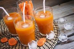 Succo di carota fresco con ghiaccio su un fondo di legno Immagini Stock Libere da Diritti