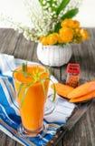 Succo di carota in tazza due di vetro su un fondo delle carote e dei fiori nel primo mattino Immagine Stock