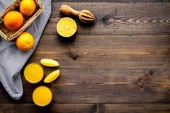 Succo di compressione dalle arance Spremiagrumi e fette di arance sullo spazio di legno scuro della copia di vista superiore del  Fotografia Stock Libera da Diritti