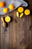 Succo di compressione dalle arance Spremiagrumi e fette di arance sullo spazio di legno scuro della copia di vista superiore del  Immagine Stock