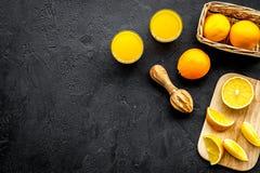 Succo di compressione dalle arance Spremiagrumi e fette di arance sullo spazio nero della copia di vista superiore del fondo Immagine Stock Libera da Diritti