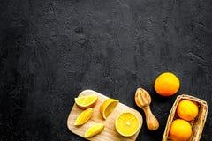 Succo di compressione dalle arance Spremiagrumi e fette di arance sullo spazio nero della copia di vista superiore del fondo Fotografie Stock Libere da Diritti