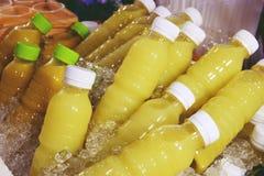 Succo di frutta casalingo in una bottiglia di plastica su ghiaccio immagini stock libere da diritti